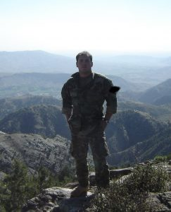 Timothy Torres wears camouflage and stands in front of mountains