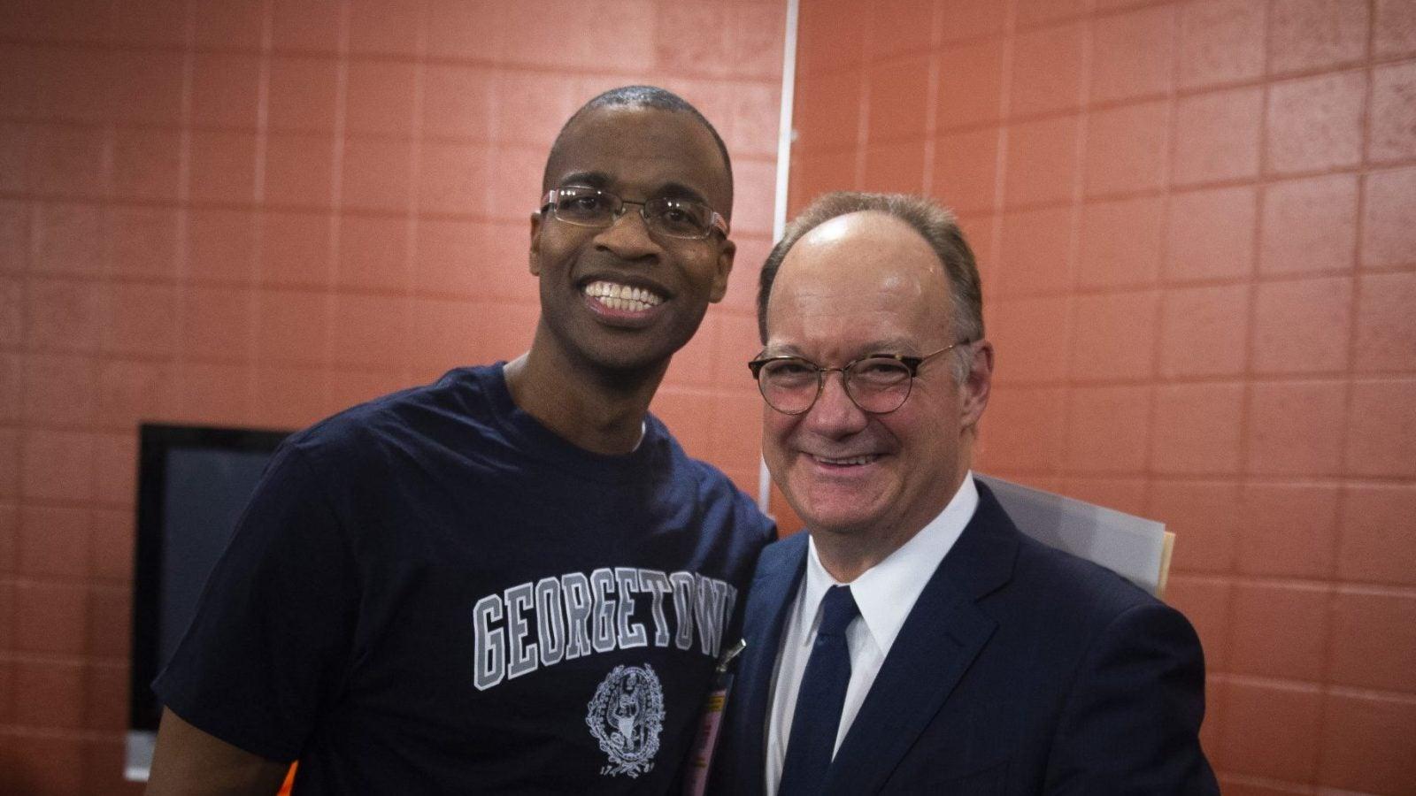 Joel Caston wears a Georgetown shirt and poses with Georgetown President John J. DeGioia