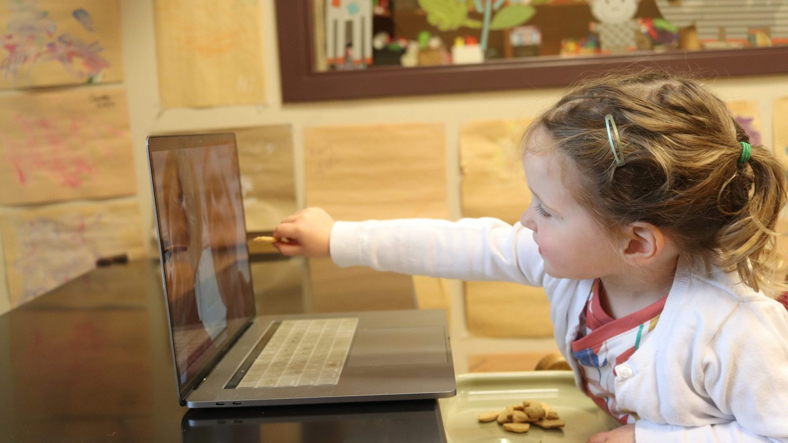 Blonde little girl reaches out to laptop screen