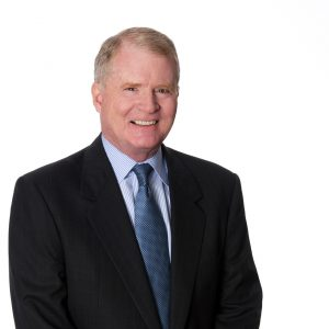Tom Reynolds wears a suit against a white background