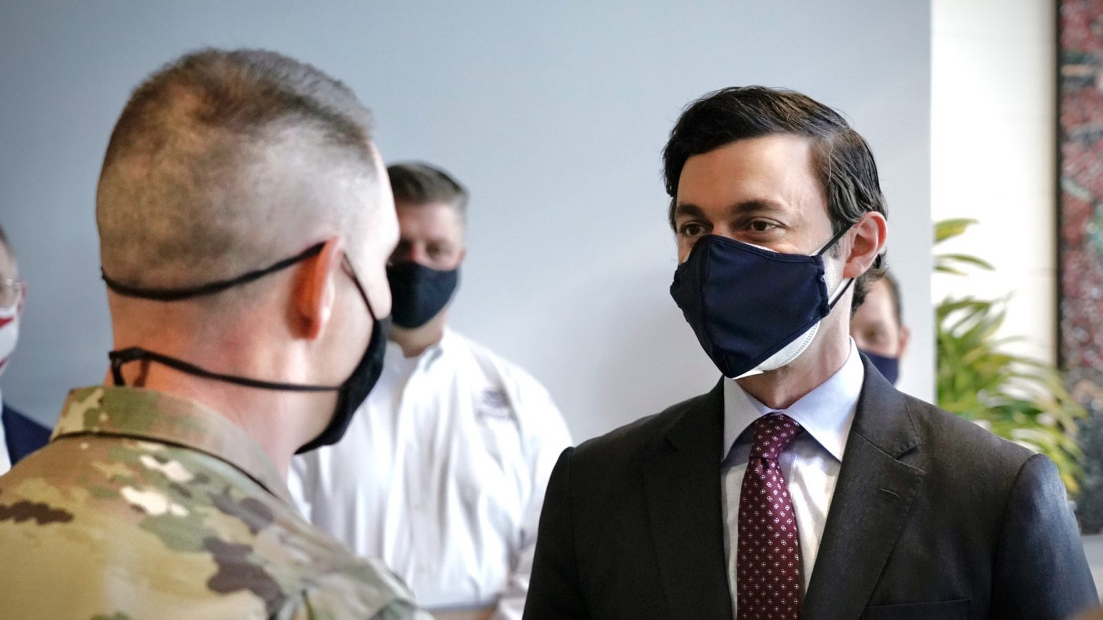 Sen. Jon Ossoff, wearing a black face mask, meets with a member of the military