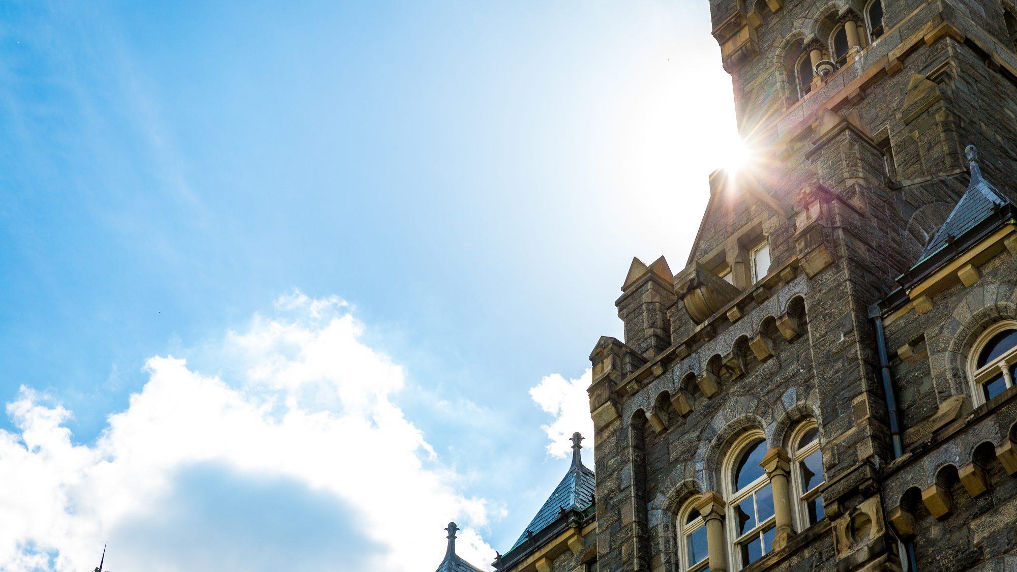 Sunburst behind the clock tower of Healy Hall