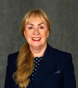Headshot of Clare Sullivan wearing a polka dot blouse and dark blazer