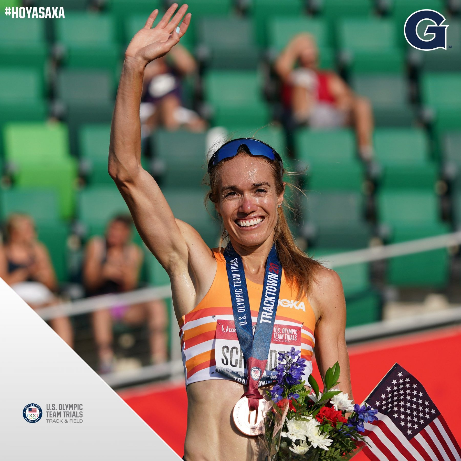 Rachel Schneider waves while wearing a medal