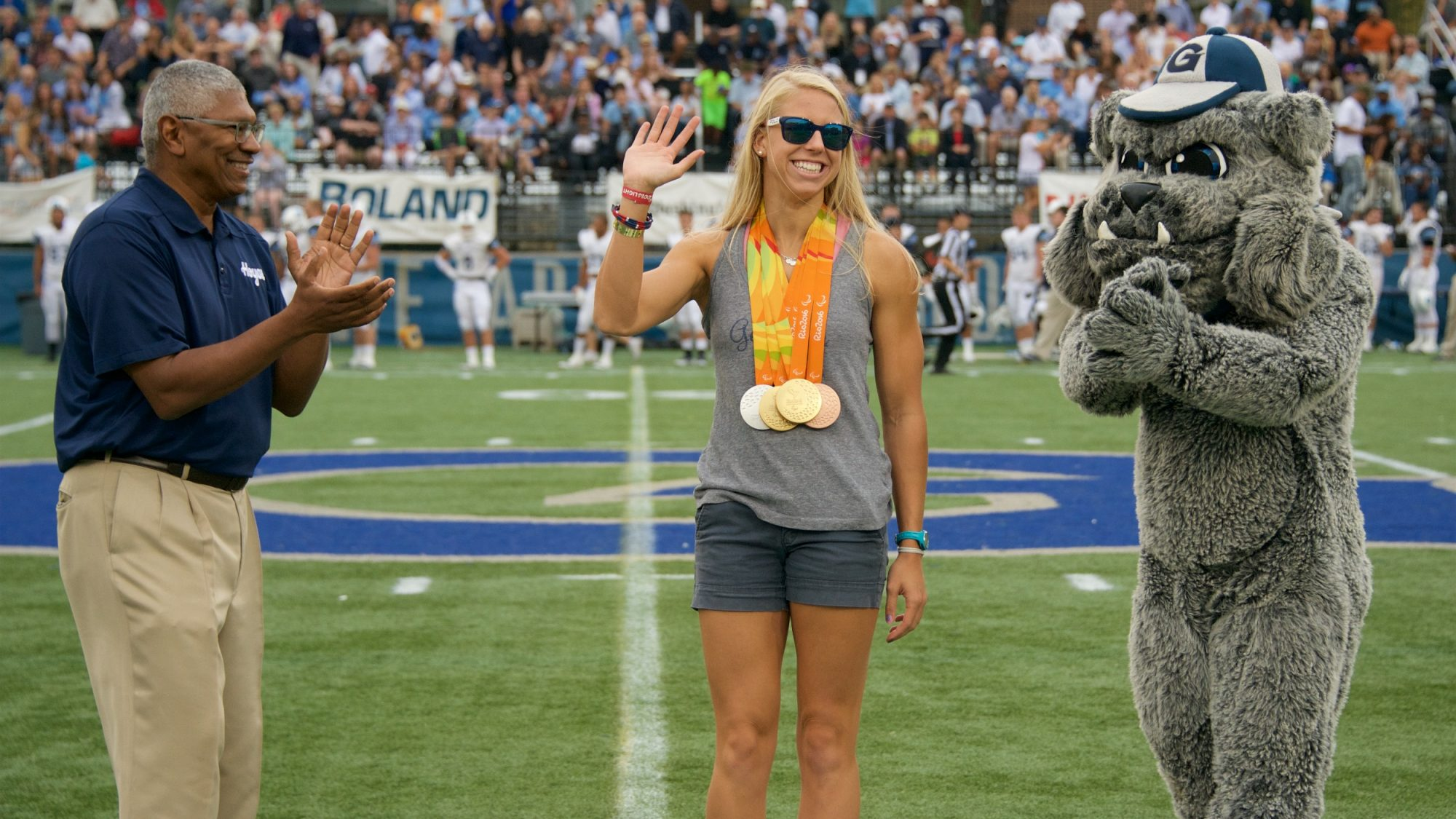Lee Reed and the Bulldog mascot applaud a waving Michelle Konkoly wearing medals