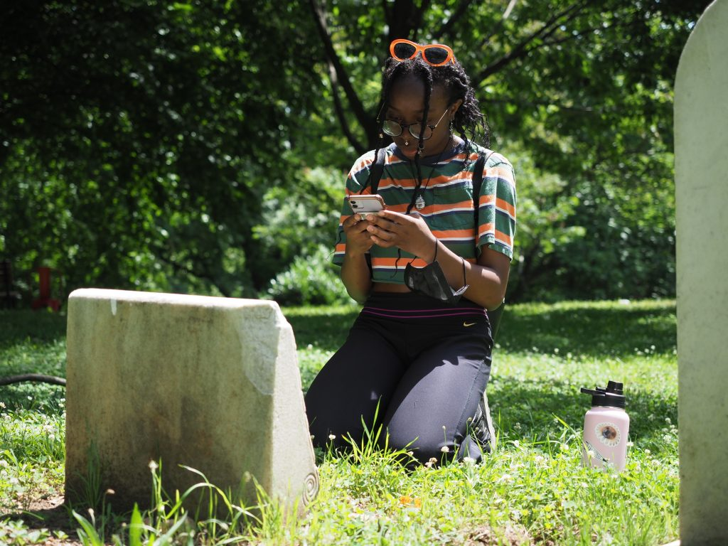 Student works on her phone kneeling in front of a headstone