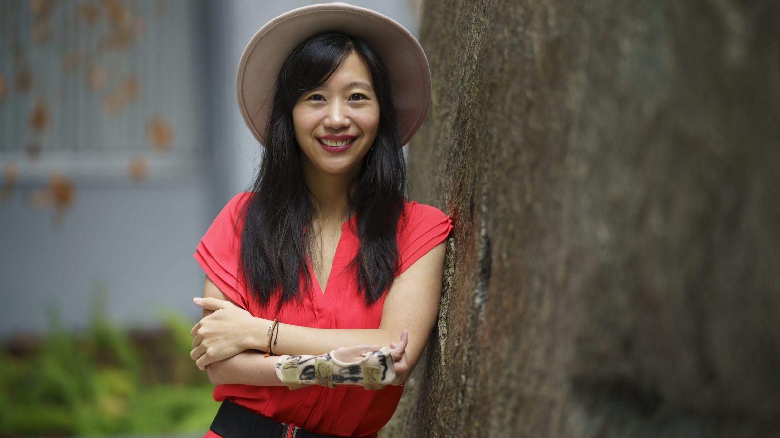 Tiffany Yu wears a hat and pink dress while leaning against a tree