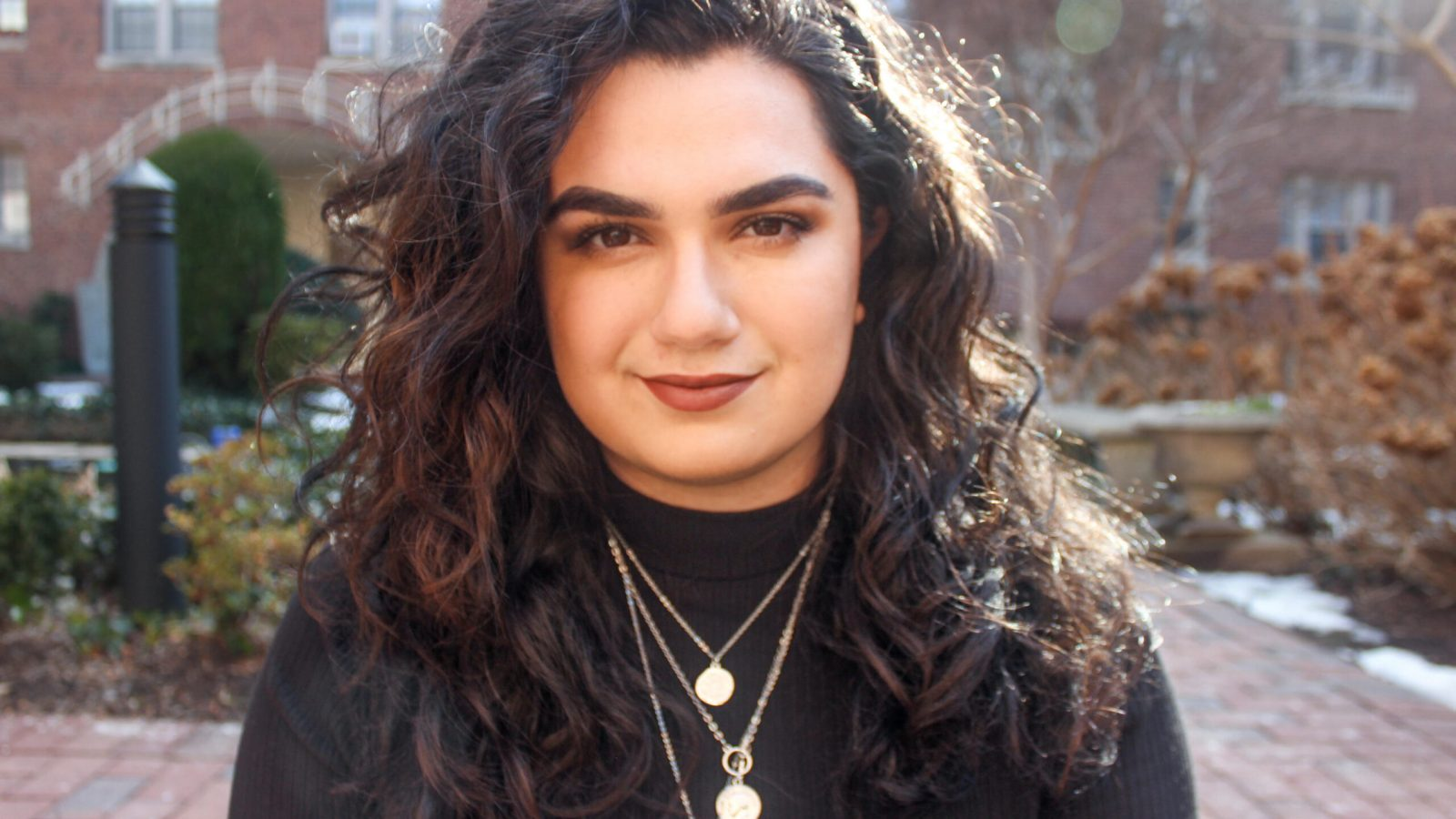 Headshot of Alanna Kronk with brick patio and buildings in the background