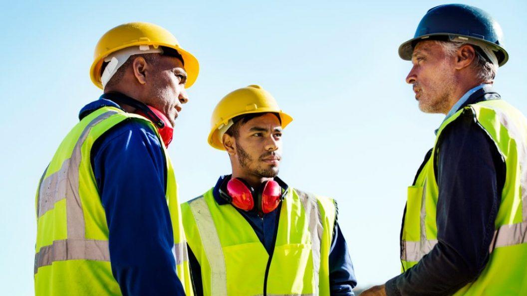 Men in neon vests and hard hats talking
