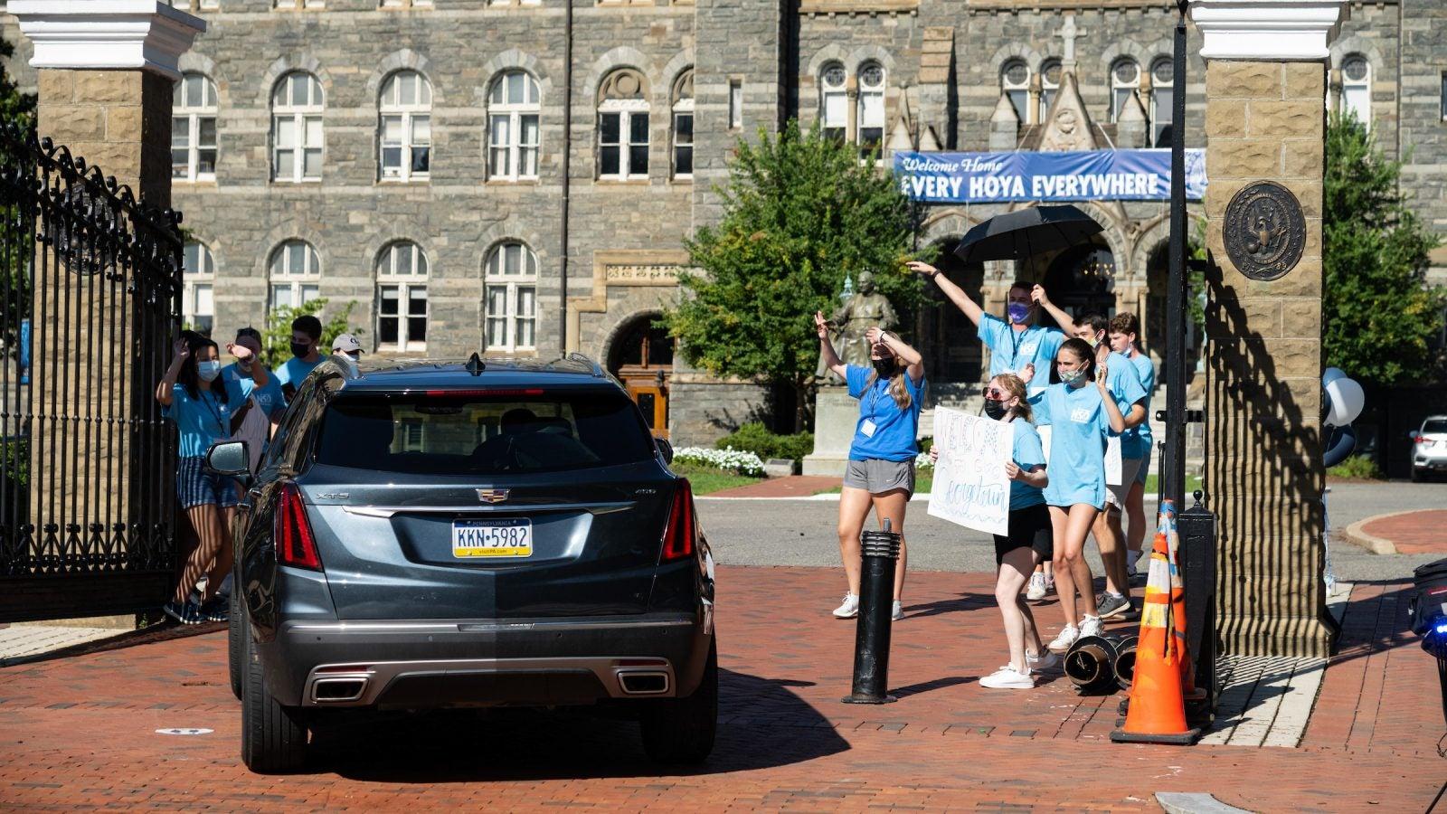 Orientation Advisors cheer as a car drives through the front gates