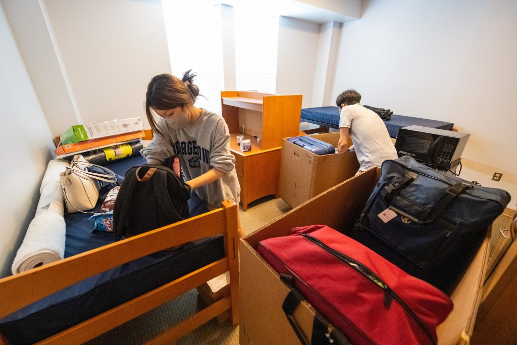 Student unpacks with her father indoors