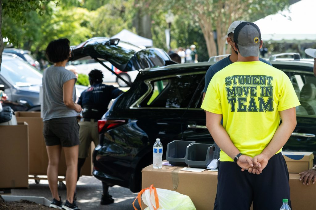 """Student wearing a neon """"Student Move In Team"""" t-shirt helps new students unload their car"""