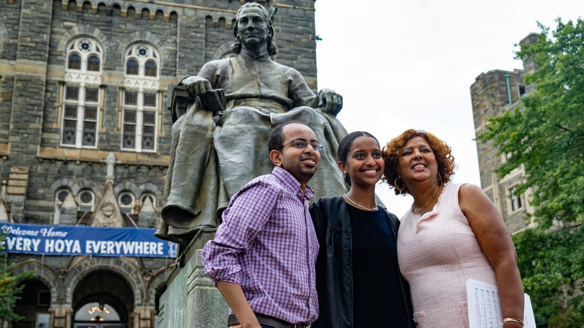 Family poses in front of John Carroll statue