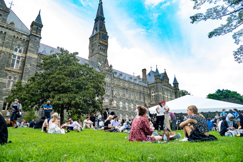 Students sit on Healy lawn in small groups