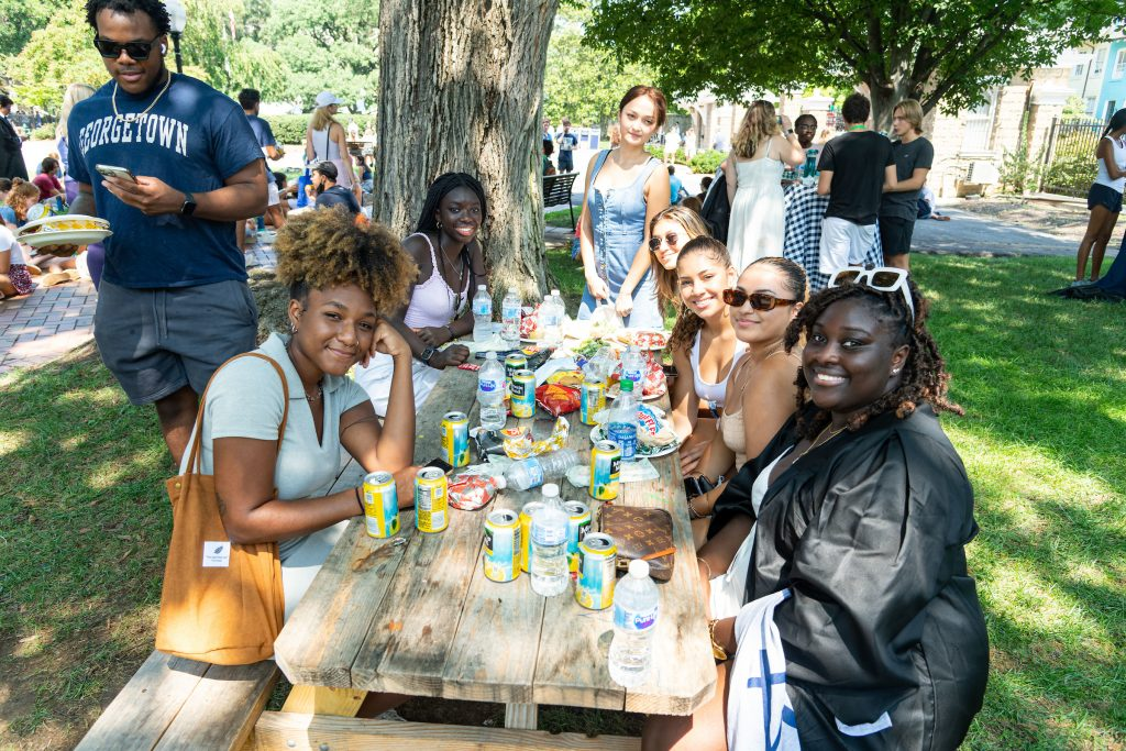 Students eat around a picnic bench