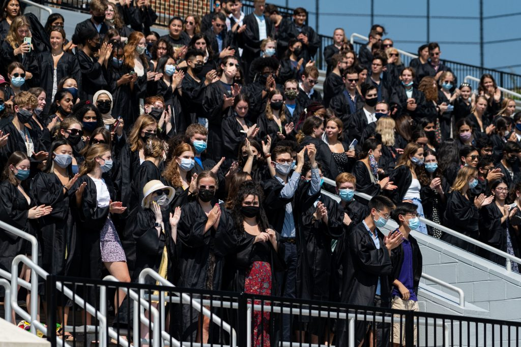 Students in on bleachers put on black robes
