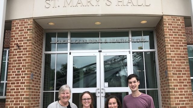 Leaders of the CURA pre-orientation program stand in front of St. Mary's Hall