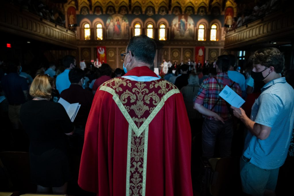 Back of a priest wearing a red robe walking through a full student audience