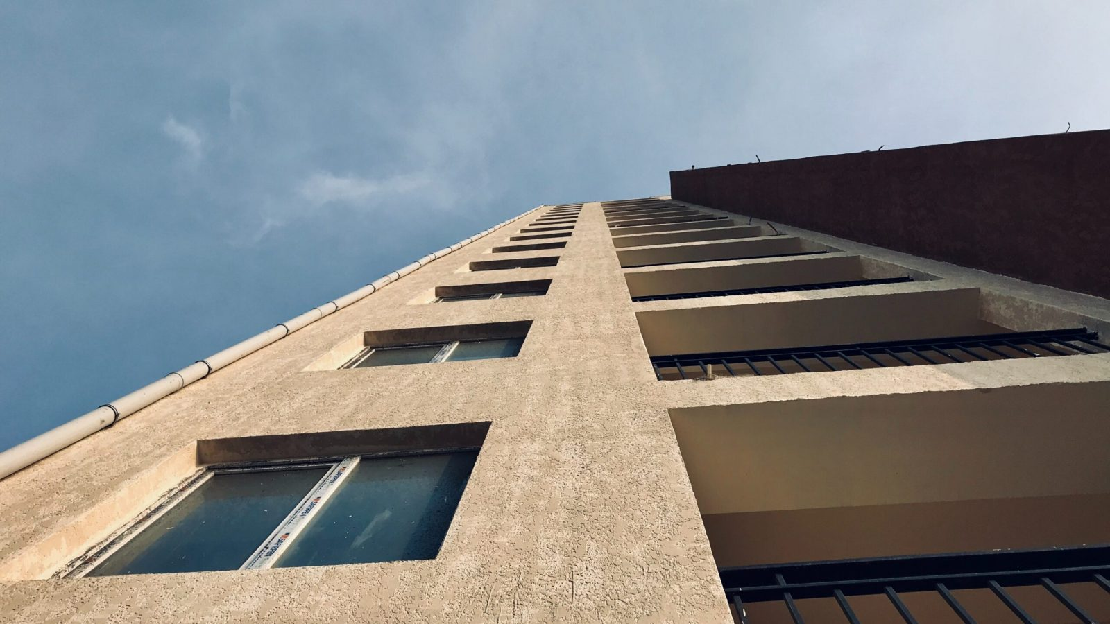 Side of a cement building looking up toward a blue-gray sky