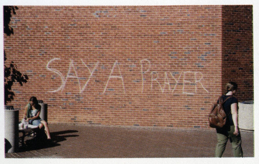 """""""Say a Prayer"""" written in chalk on a brick building"""