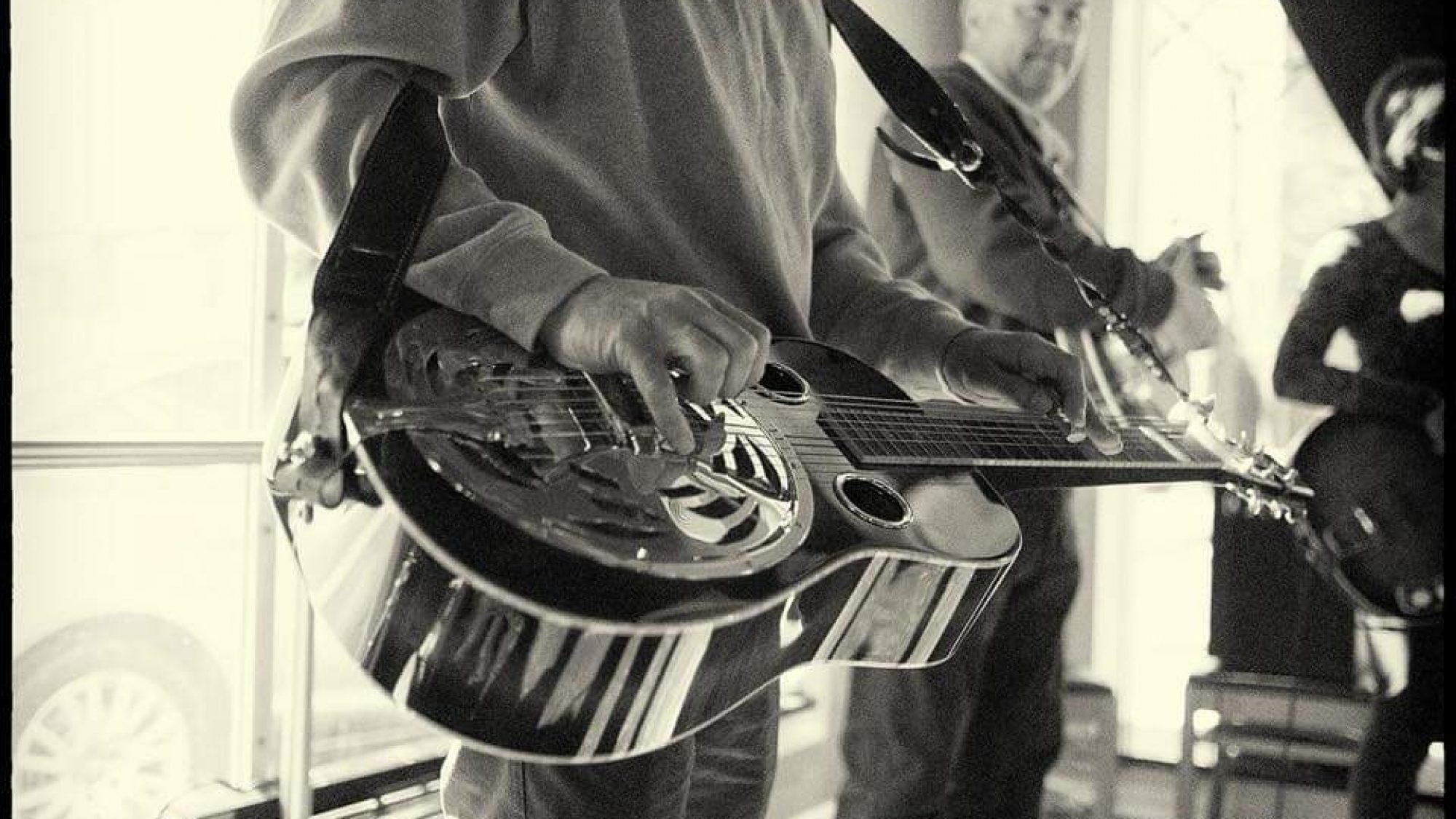 A black and white picture of Alex Sens holding a guitar