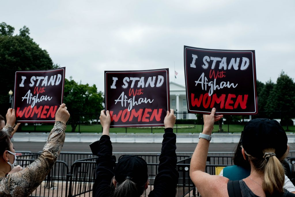 """Women holding signs that say """"I stand with Afghan Women"""" in front of the White House"""