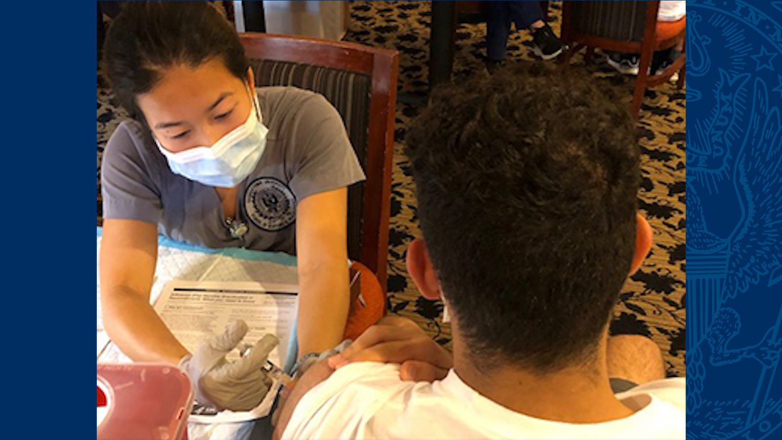 Nursing student wearing a mask gives a flu shot