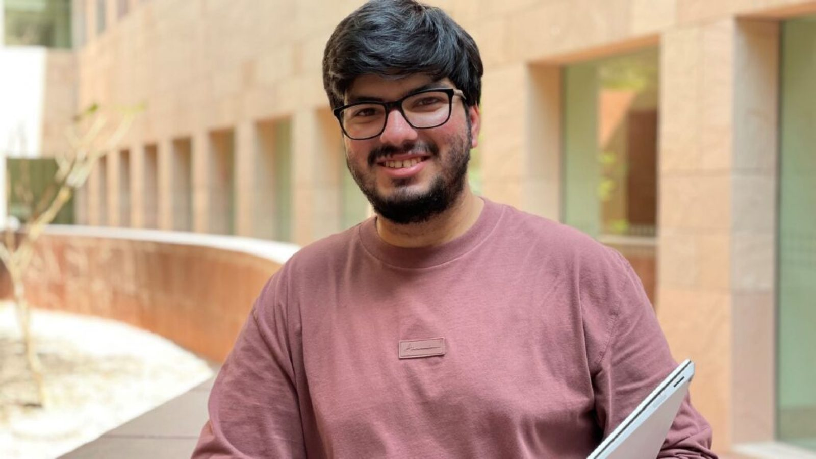 Kartikeya Uniyal wears glasses and a dark pink shirt