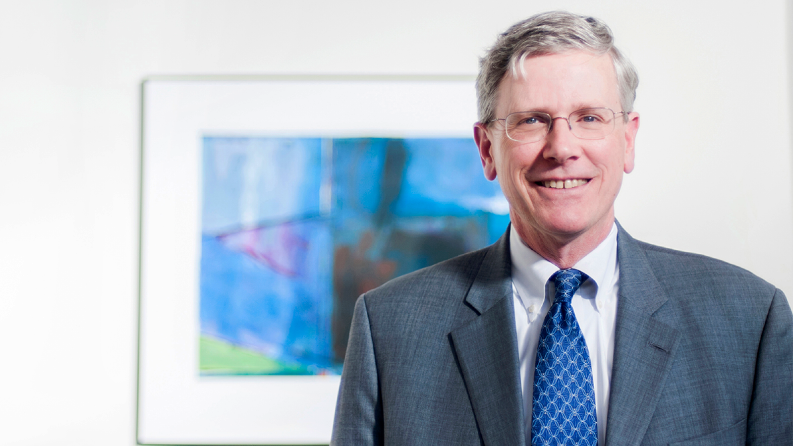 John Monahan wears a suit in front of a blue picture on white wall