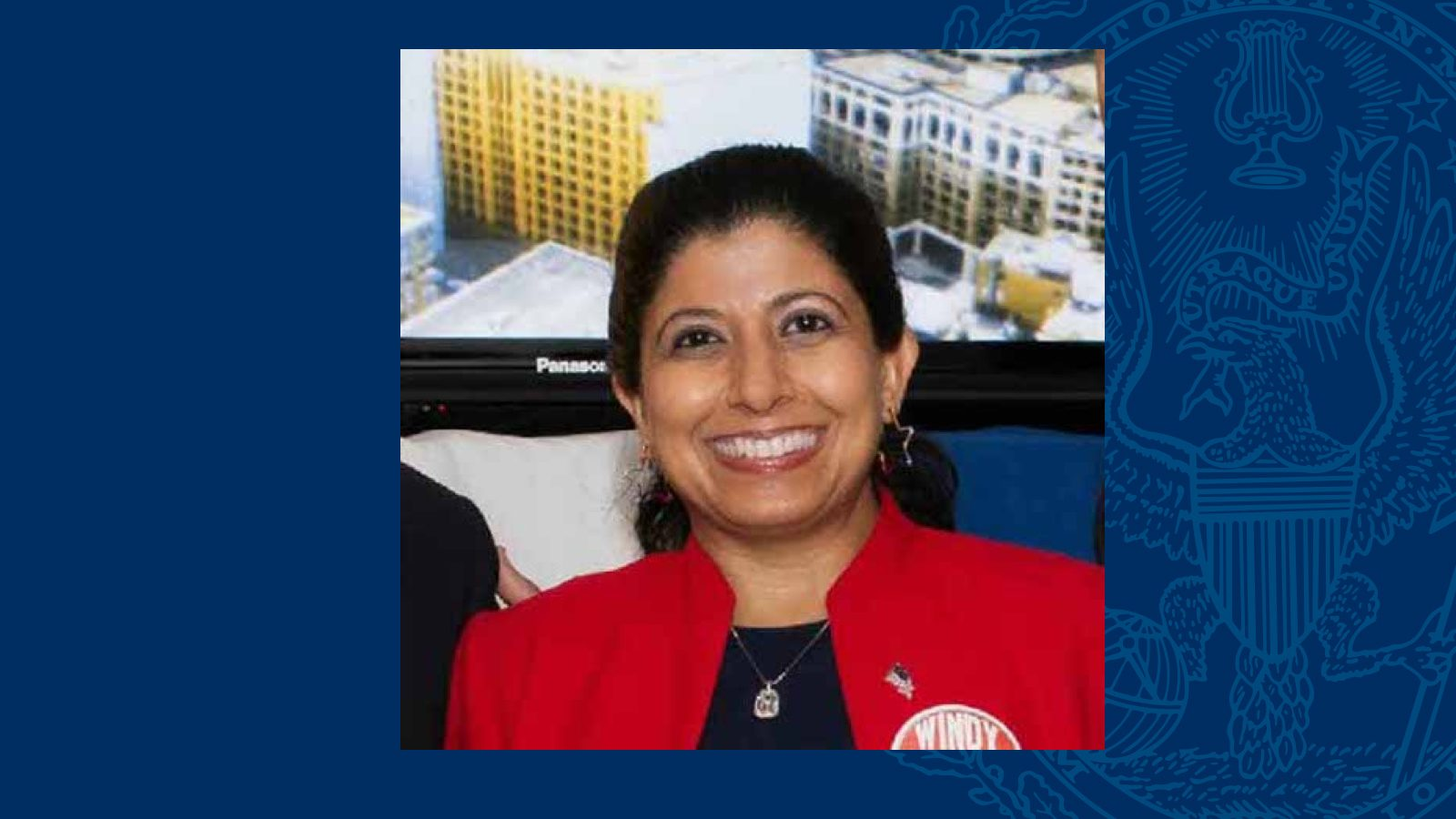 Nazima Razick wears a red blazer in a square headshot on a blue background