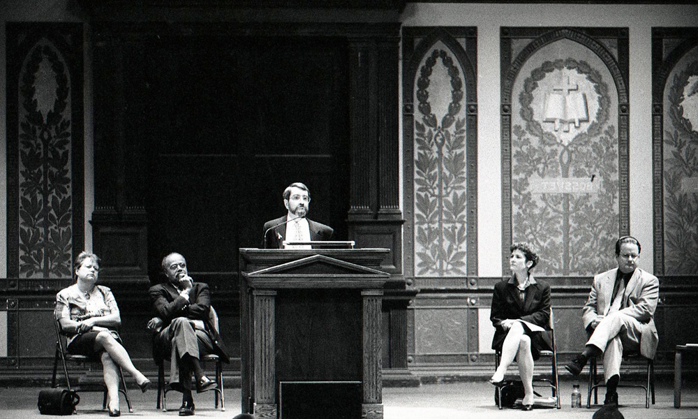 Black and white image of five administrators speaking from a stage