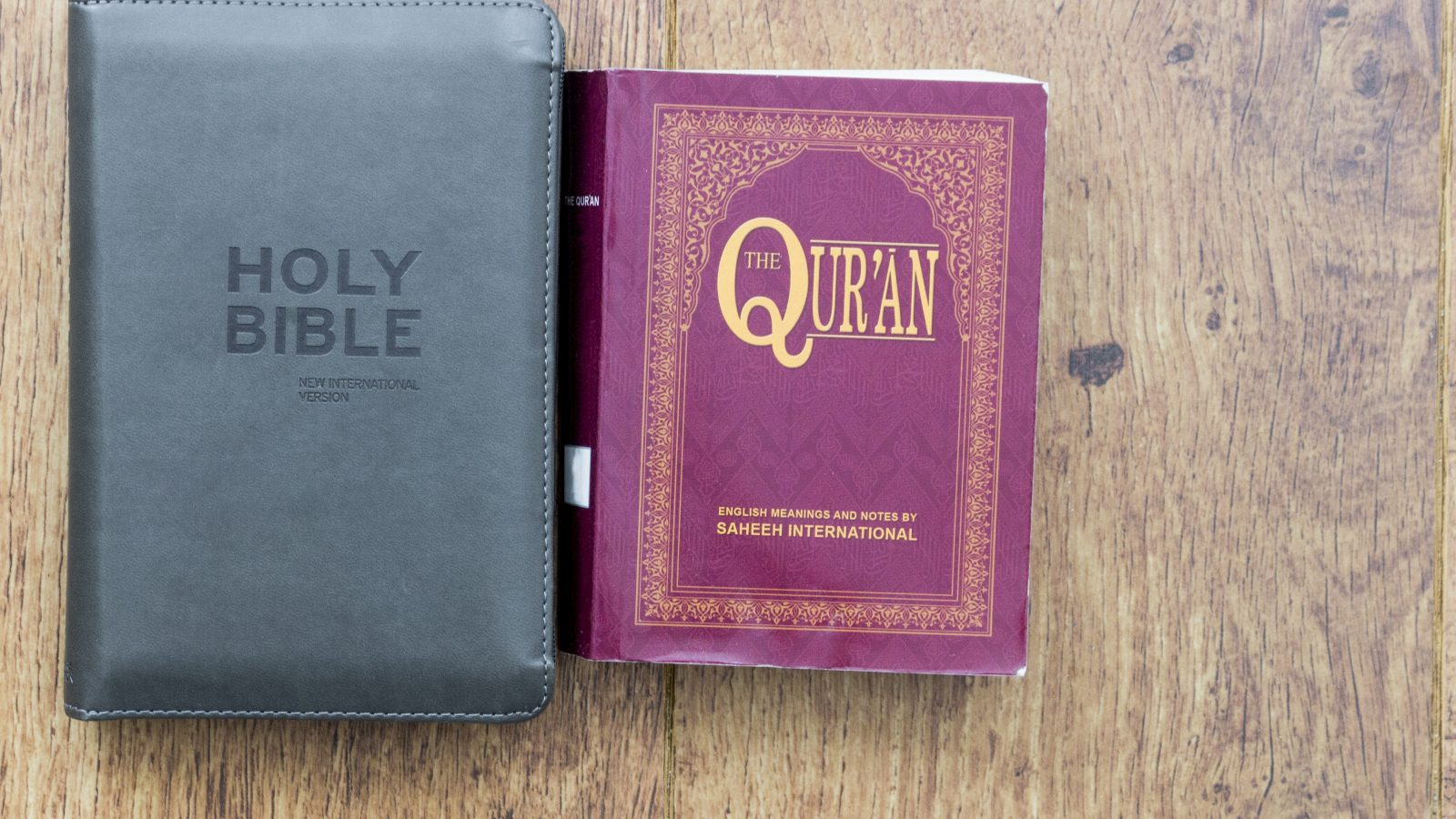 Black Holy Bible next to a Red Qur'an on a wood surface