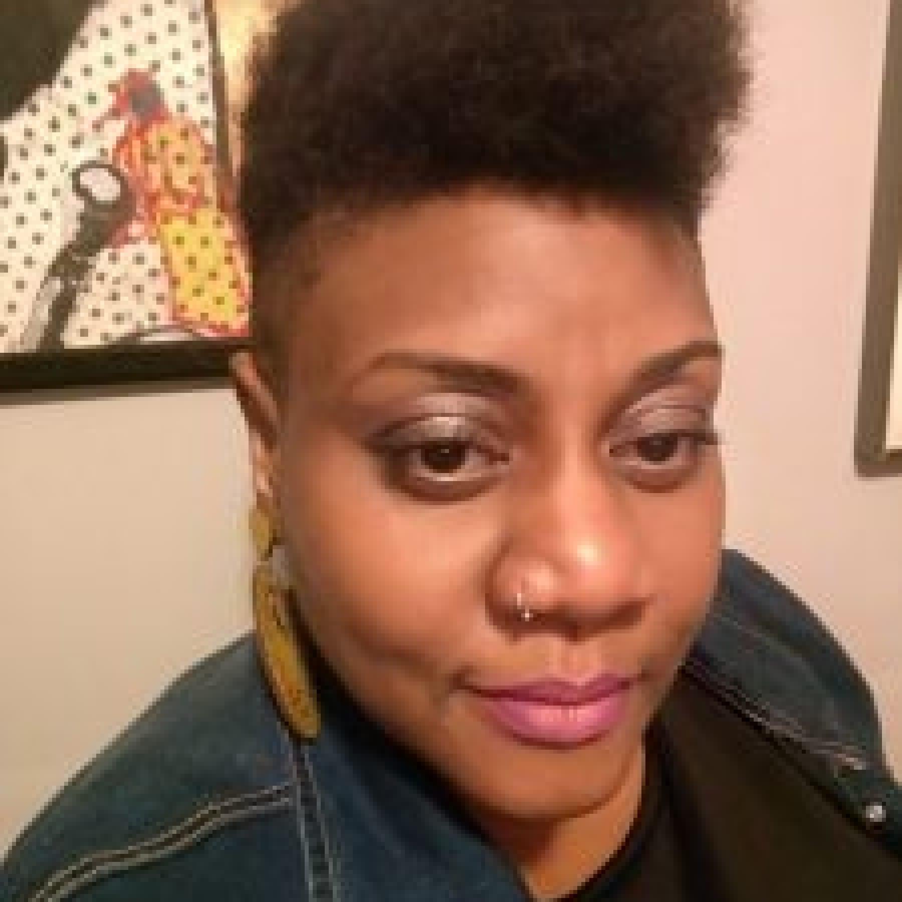 Headshot of Amena Johnson wearing a jean jacket and earrings
