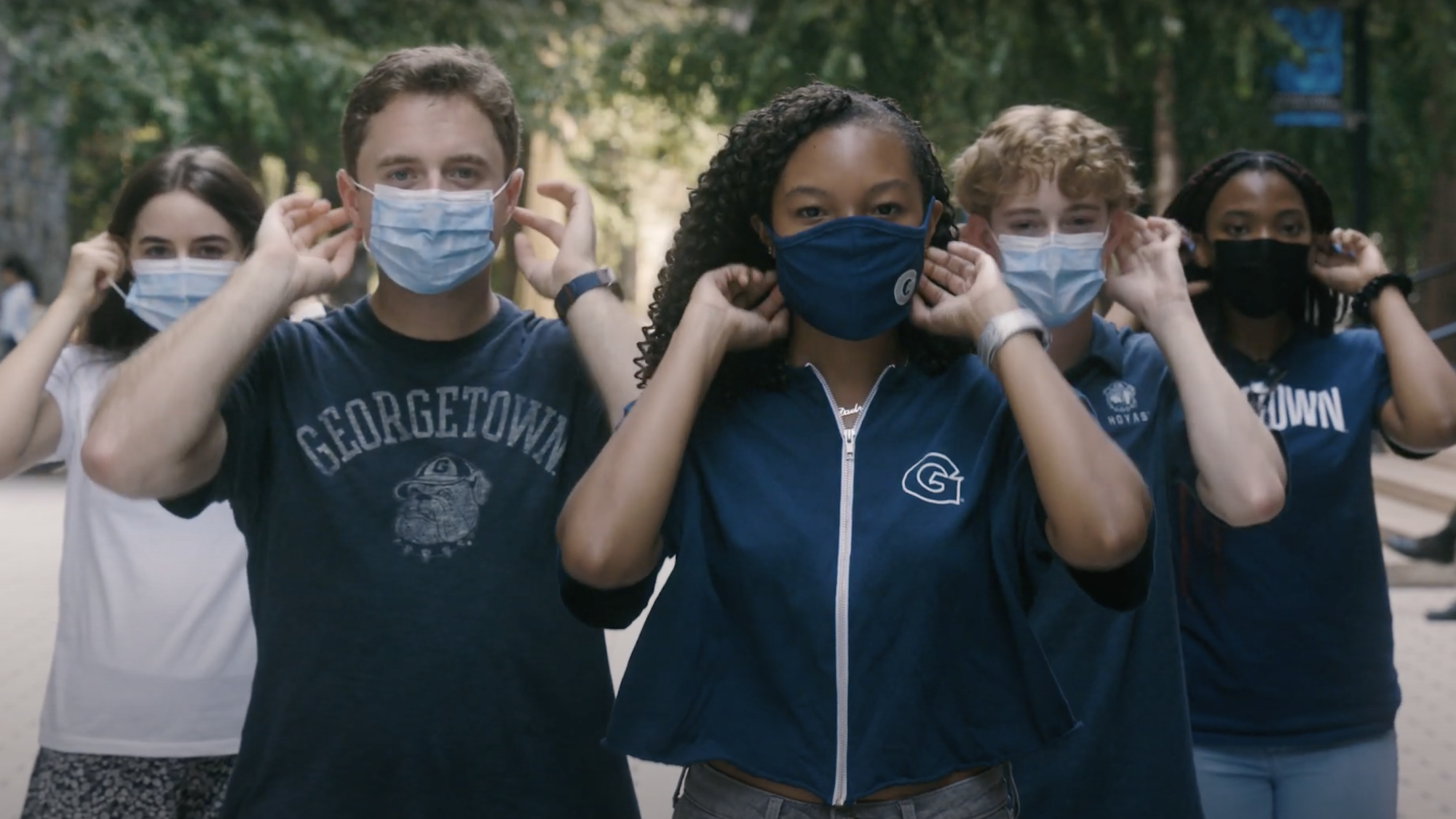 Five students wearing Georgetown apparel put on their masks
