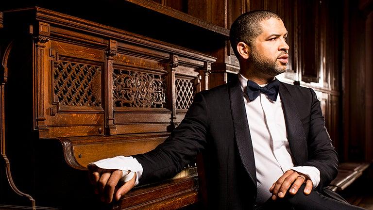 Jason Moran in tuxedo sitting with hand on piano