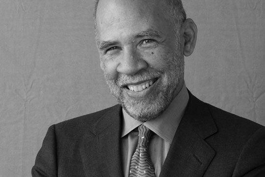 John A. Payton smiles in a black and white headshot.