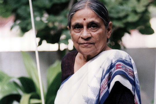 Ela R. Bhatt looks at the camera in a headshot.