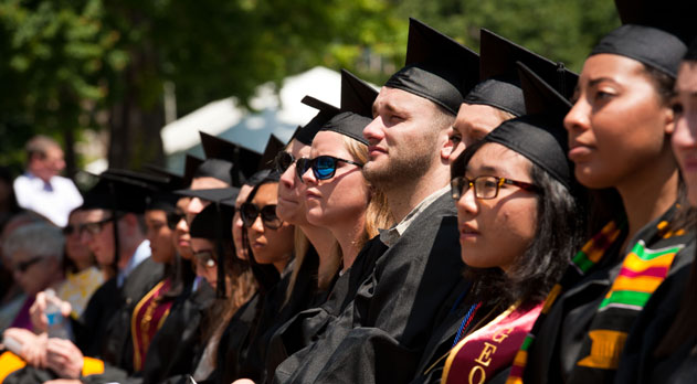Students dressed in caps and gowns look on at commencement.