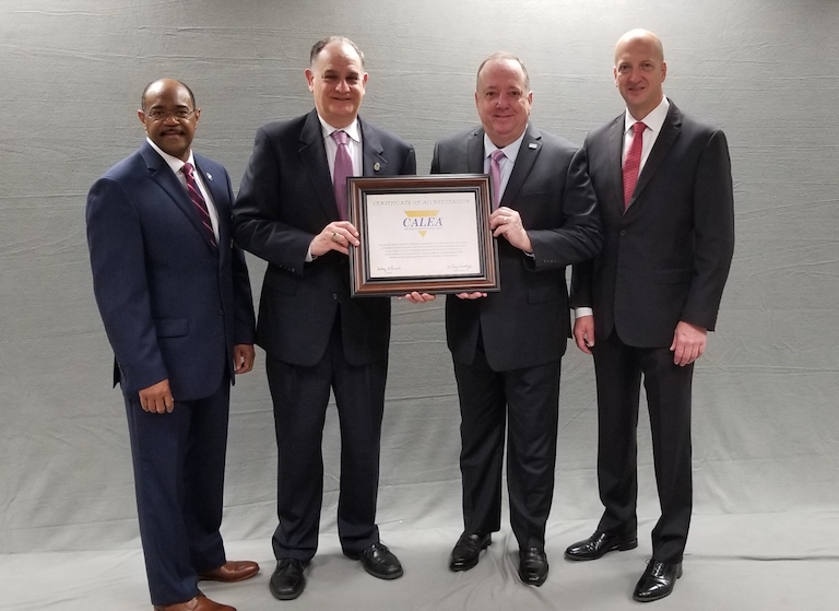 Four men stand in front of a gray background, with the two in the middle holding up the CALEA award.