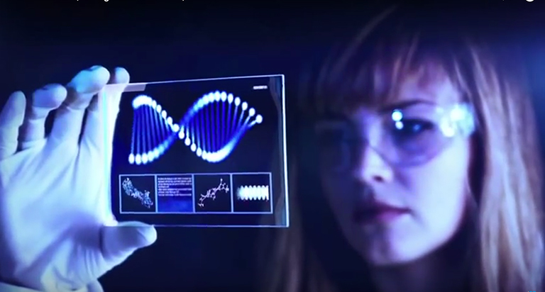 Woman in a white lab coat,goggles and gloves holds up a high-tech slide of a cell to the light as she conducts research