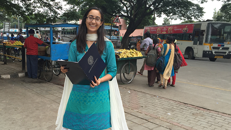 Chandini Jha (C'16), dressed in a bright turquoise dress, smiles and poses on a busy street in India.