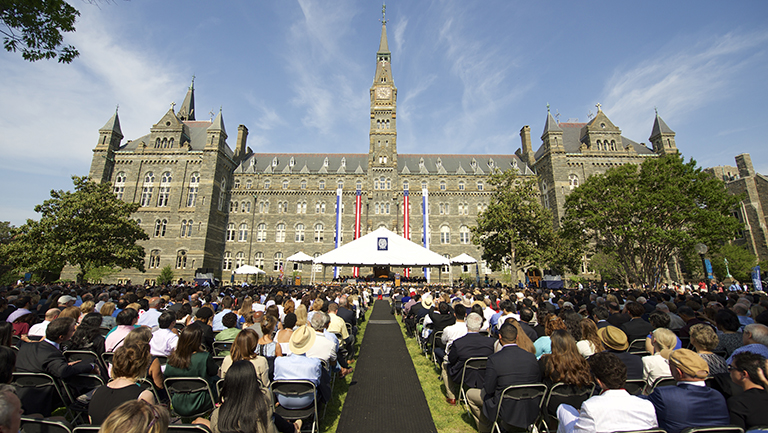 Students sitting in chairs in cap and gown on the Healy building lawn waiting for commencencement