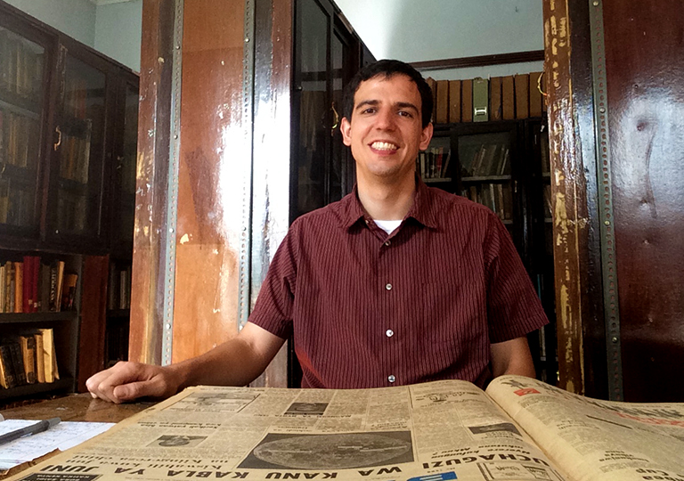 Andy Marshall sits at a desk with old periodicals on it and old wooden cases filled with books in the background.