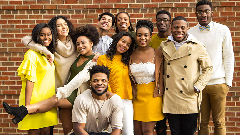 Members of Black Student Alliance leadership pose together dressed in yellows, khakis and greens.