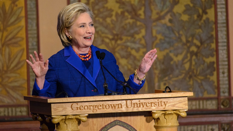 Hillary Rodham Clinton wears a blue suit as she gestures while speaking at a lectern in Gaston Hall.