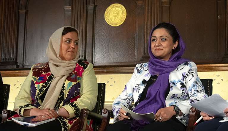 Roya Ramani and Palwasha Kakar sit in chairs wearing hijabs