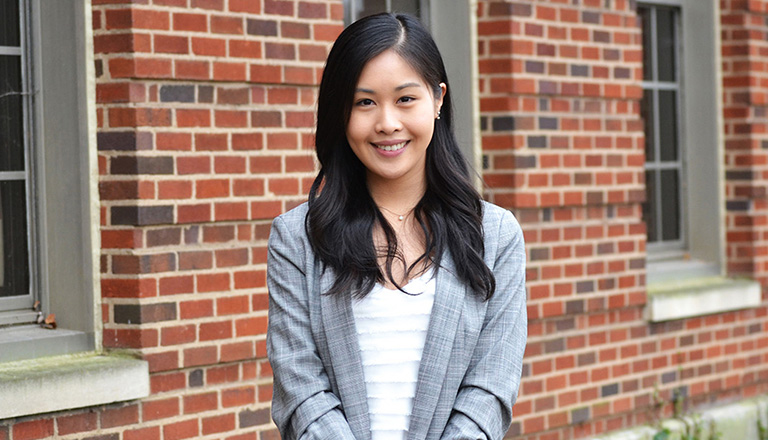 Sally Huang in front of brick building with window