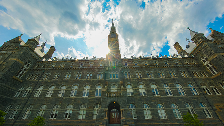 Photo of Healy building on Georgetown campus with sunlight behind its tower