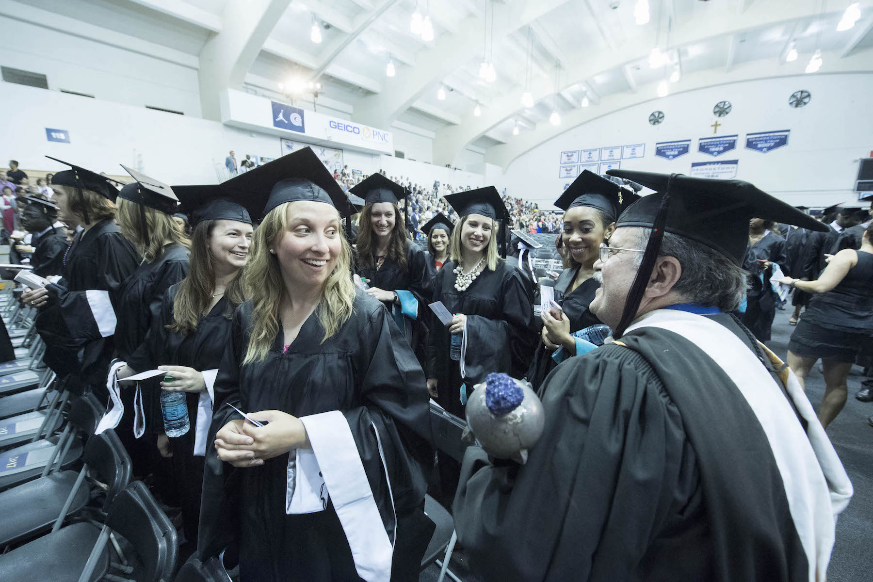 SCS graduates and administrator carrying the university mace