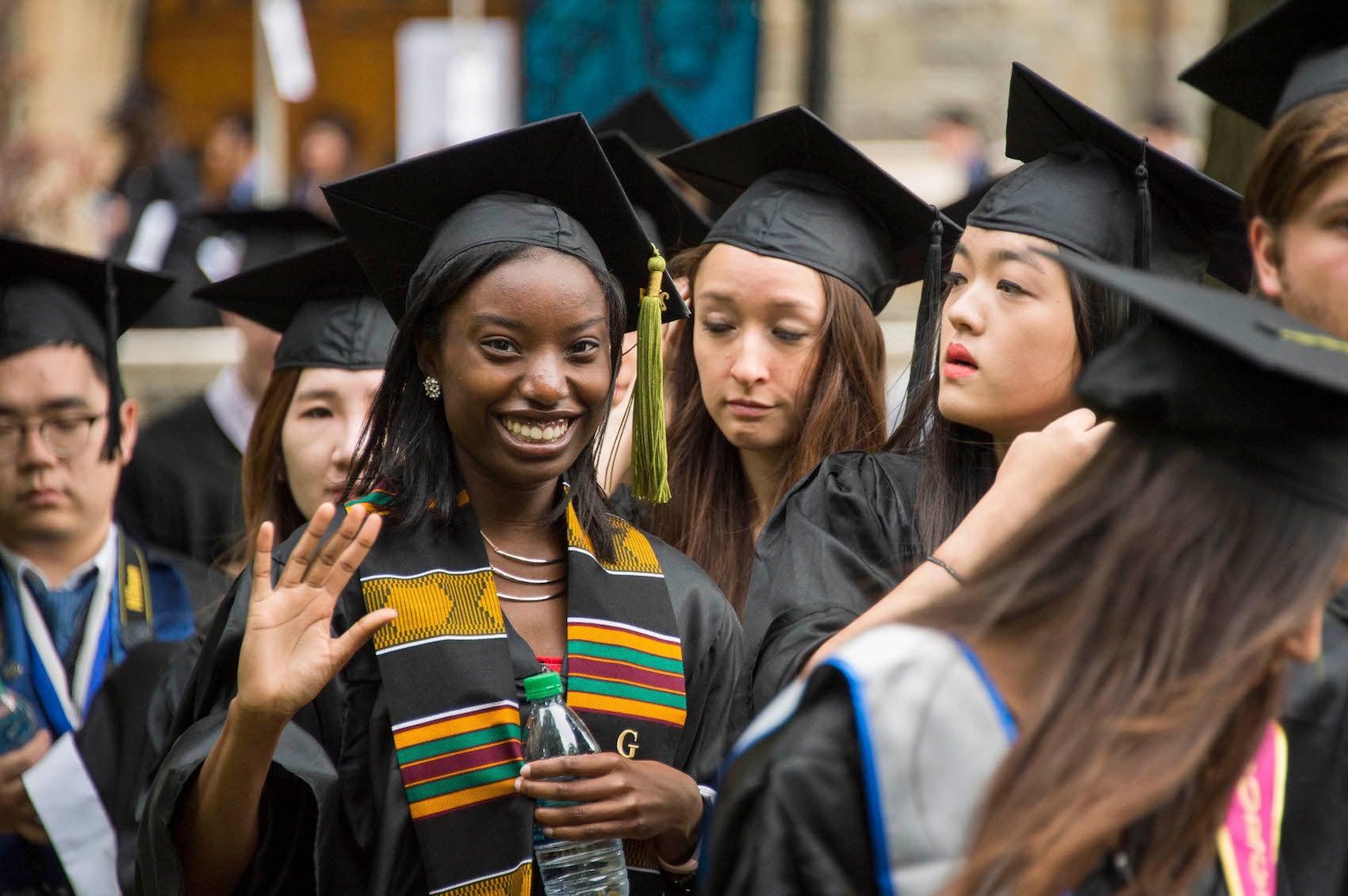 Smiling graduates in commencement attire